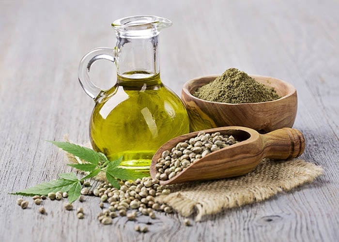 Hemp oil in a glass jar and hemp seeds